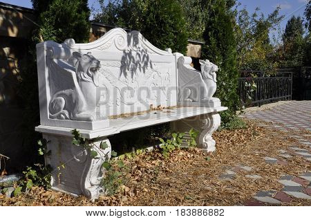 carved white bench with lions in the Park under a tree
