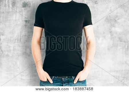 Front view of casual male in blank black shirt on concrete background. Retail concept. Mock up