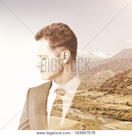 Side portrait of young european businessman on landscape background. Double exposure