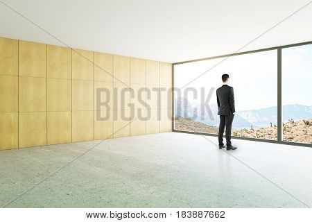 Side view of businessman looking out of window in unfurnished loft interior with panoramic landscape view. 3D Rendering
