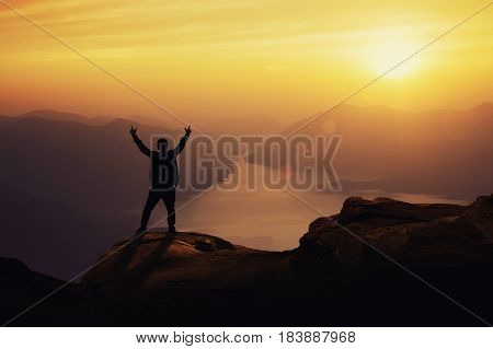 Young happy tourist on top of a mountain enjoying valley view before sunset.