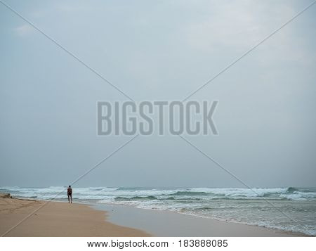 Picture of a man from behind walking on a beach under rain