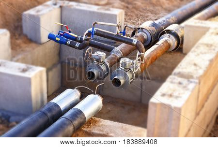 The process of installation of the distribution unit heating network. Frame for connecting pipes in the trench of sand.