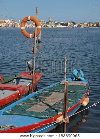 Chioggia, Italy. Two boats in the lagoon. On the pole a life bucket.