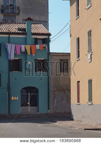 Alley at Chioggia, Italy. Colored houses and cloths. The sign says