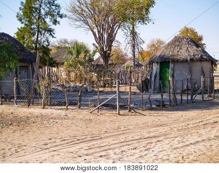 Small African village compound by dusty road homes and people of Gweta Botswana