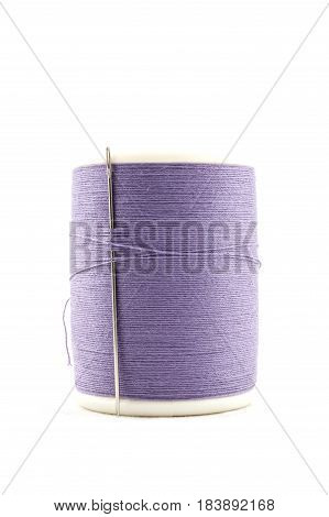 Spool Of Purple Thread And Needle On White Background