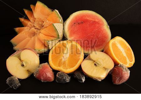 Various fruits packed in plastic film on black background