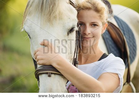 Beautiful young blonde woman portrait with her horse