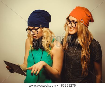 two hipster girls friends use digital tablet, studio shot over gray vackground