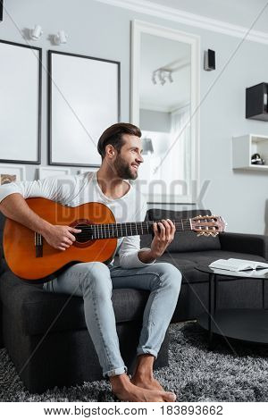 Image of young man sitting on sofa indoors at home while playing on guitar. Looking aside.