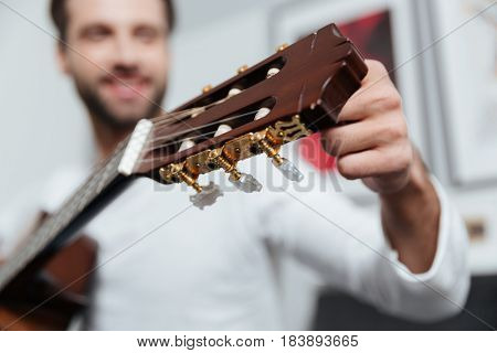 Image of young happy man sitting on sofa indoors at home while playing on guitar. Focus on guitar.