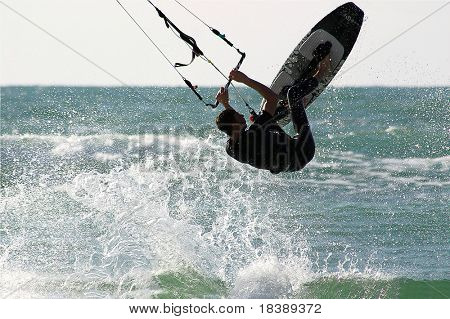 Kitesurfer jumps over the water during training on Mediterranean sea.