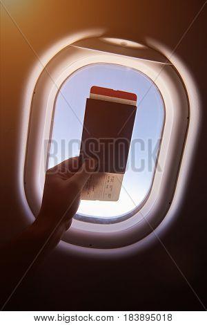 Hand Holding Passport With Plane Ticket