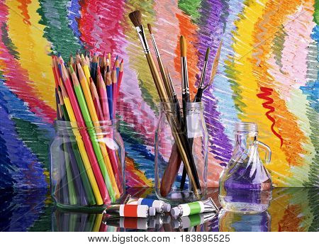 On a glass dark table are banks with colored pencils and brushes for drawing. Near them lie tubes with paint. Tools for drawing on a bright multi-colored background. Reflection.