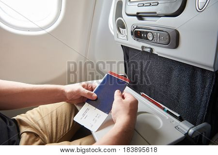 Man In Airplane With Passport In Hand