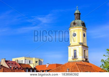 Town hall tower over red tile roof on central square of Kosciusko Market in Bialystok Poland. Town hall in Baroque style was built 1745-1761 architect Ian Klemm. Museum of Podlasie