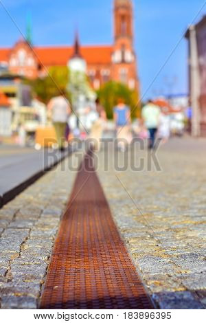 Pavers in central square of Kosciusko Market. On background Cathedral Basilica of Assumption of Blessed Virgin Mary in Bialystok Poland. Selective focus on the pavement blurred abstract background