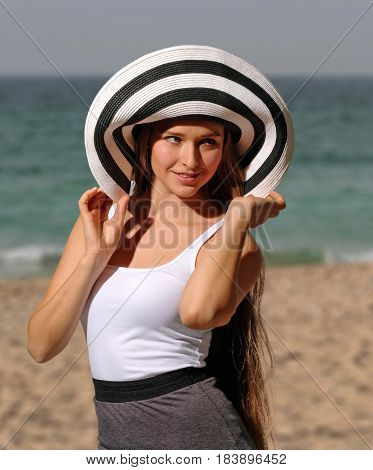 Beautiful young woman in white t-shirt and brimmed hat on the beach. Her sight is directed to the right. She tilting hat to the neck. She smiling, open mouth.