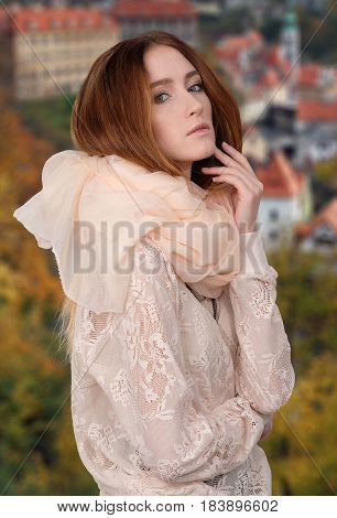 Red-haired pretty woman with blurred Krumlov on the background. She dressed in elegant lace blouse and light scarf around the neck. Her hand bent at the elbow, near face.