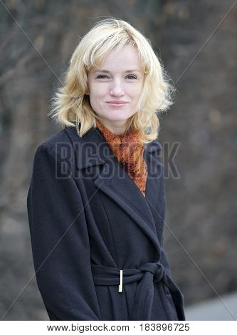 Portrait of a beautiful young blonde on a dark blurred background. She is dressed in a black long coat with a bright shawl around her neck. She holds her hands in pockets