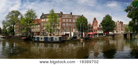 Panorama of city canal (Amstel river) and old houses in historical center of Amsterdam, Netherlands.