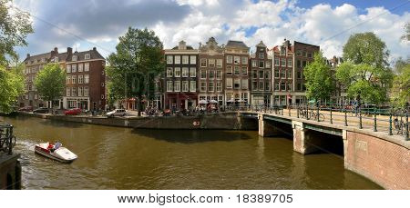 Panorama of city canal (Amstel river), bridge and old houses in historical part of Amsterdam, Netherlands.