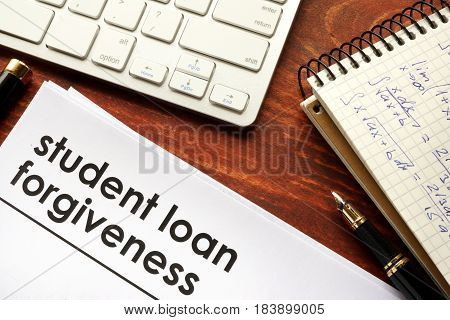 Document with title student loan forgiveness and pen.