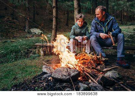 Father with son warm near campfire drink tea and have conversation