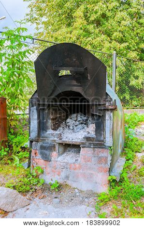 Old iron shabby garden stove with ash remains inside
