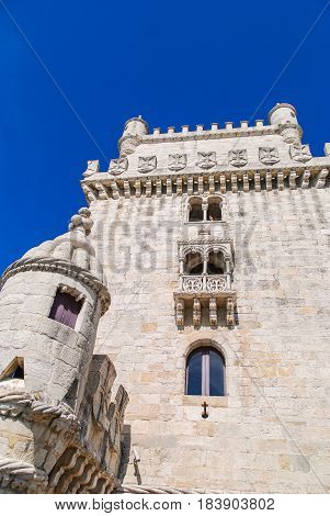 White stone Belem tower in Lisbon, Portugal low angle view with deep blue sky above