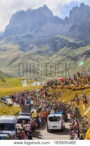 Col du Glandon France - 23 July 2015: The official ambulance drives behind the peloton riding in a beautiful curve at Col du Glandon in Alps during the stage 18 of Le Tour de France 2015.