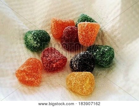 Candy gummies above a white napkin. Ten candy gummies with different colors. Three candy gummies Orange, two candy gummies red, three green, one black and one yellow