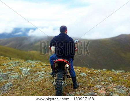 Young biker at the hill looking at the horizon. Biker looking at the mountains. Biker parked at the mountains looking at the landscape. Young male argentinian biker