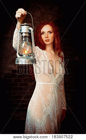 Portrait of a lovely young redhead woman with kerosene lamp