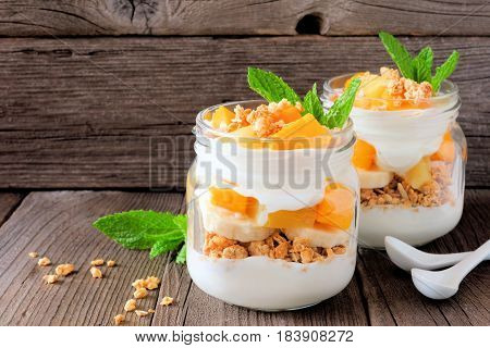 Healthy Mango And Pineapple Parfaits In Mason Jars With A Rustic Wood Background