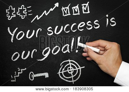 Your success is our goal. Blackboard or chalkboard with hand and chalk. Written and various symbols of success. Motivational achievement concept