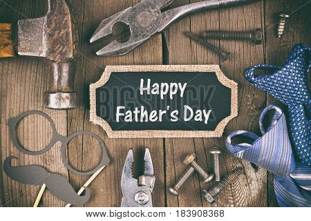 Happy Fathers Day message on a chalkboard tag with frame of tools and ties on a wooden background, vintage styling
