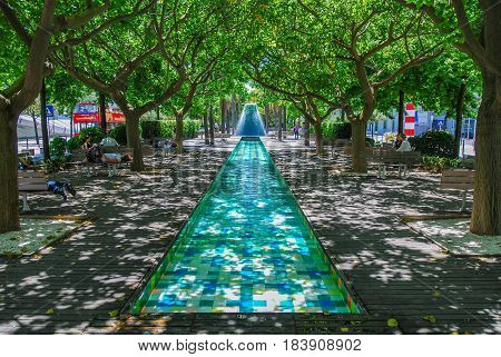 Turquoise fountain in the shade of beautiful trees, Lisbon, Portugal