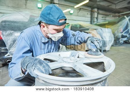 repair mechanic worker with light alloy car wheel disk rim