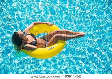 Aerial View Of Young Brunette Woman Swimming On The Inflatable Big Donut In Pool