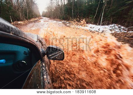 Suv 4wd car rides through muddy puddle, off-road track road, with a big splash, during a jeeping competition