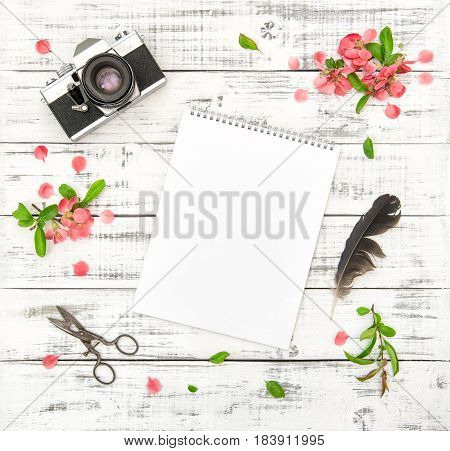 Flat lay with paper sketchbook photo camera pink spring flowers on white wooden background