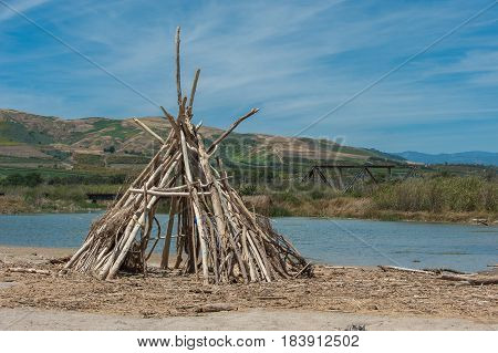 Beach hut made of driftwood logs on estuary shoreline.