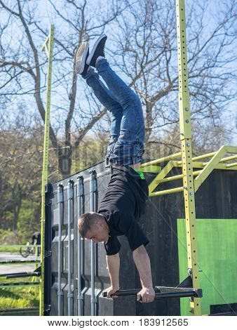 Young Athlete doing a Hand Stand On Parallel Bars In An Outdoor Gym - Street Workout Exercises