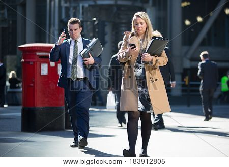 London, UK - March 15, 2017: Young woman with mobile phone in the city of London. Modern busy business life