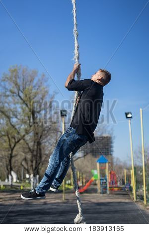 Young Athlete climbing up the Fitness rope. climb exercise in outdoor crossfit gym