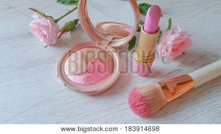 Set of cosmetics in delicate pink color on white wooden background