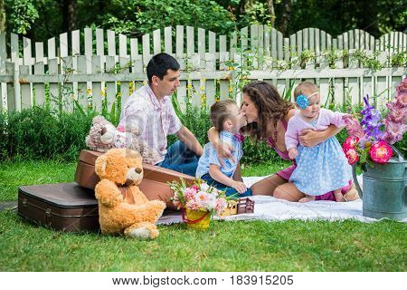 Young couple sitting in the lawn with the children and are kissing them in Lviv, Ukraine.