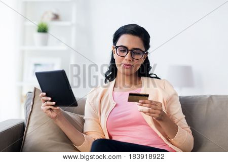 people, internet bank, online shopping, technology and e-money concept - happy woman with tablet pc and credit card at home